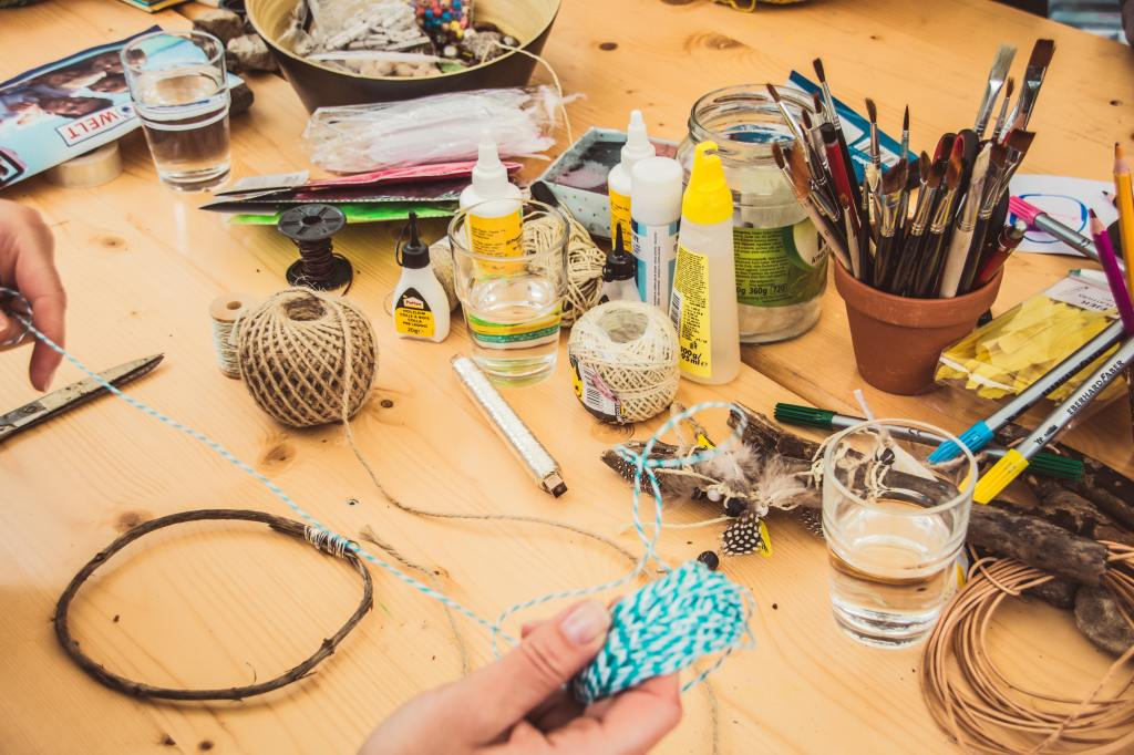 Desk full of crafting materials Photo by Jasmin Schreiber on Unsplash